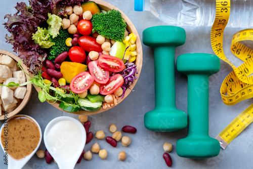 Fresh vegetable salad and healthy food for sport equipment for women diet slimming with measure tap for weight loss on black background concrete Fototapeta