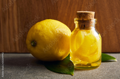 Whole lemon with bottle of essential oil on dark surface