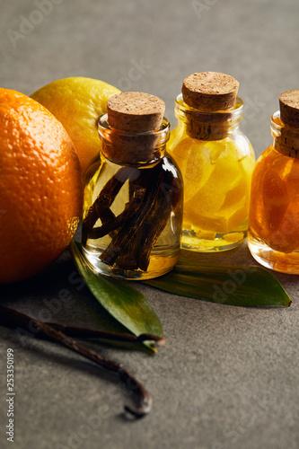 Bottles of essential oil with lemon, orange and vanilla on dark surface