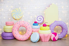 Children Party Background - Set Of Huge Artificial Sweets And Pastry Decorations Over White Brick Wall