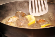 Steaming Fresh Clams In Wine & Garlic Sauce With Lemon