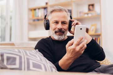 Senior bearded man relaxing listening to music