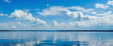 Fototapeta Na sufit - Panorama of calm lake, Kama river blue sky with clouds reflected in the water.