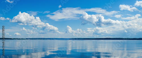 Panorama of calm lake, Kama river blue sky with clouds reflected in the water.