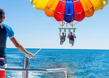 Happy Couple Parasailing On Miami Beach In Summer. Couple Under Parachute Hanging Mid Air. Having Fun. Tropical Paradise. Positive Human Emotions, Feelings, Family, Travel, Vacation.