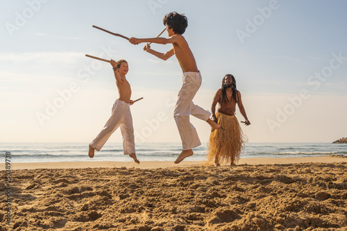 Fotografía  Boys in white pants practicing capoeira (Brazilian martial art that combines ele