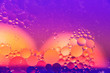 Leinwandbild Motiv Abstract macro photography. Abstract background. Orange with purple color. Distortions in water with drops of oil. Bright abstraction, ultraviolet. Circles on the water