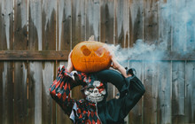 Boy Dressed In Costume Holding Jack O' Lantern While Standing Against Fence In Backyard