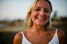Close-up Portrait Of Happy Woman Standing At Beach Against Sky During Sunset