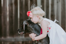 Side View Of Girl Kissing Dog Outdoors