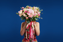 Perfect Gift. Wonderful Flowers On Womens Day. Tender Smiling Brunet Woman Holding In Front Of Face The Bouquet Of Spring Flower, Isolated Over Blue Studio Background. Space For Text