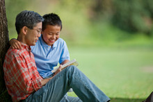 Happy Father And Son Reading A...