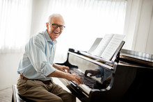 Smiling Senior Man Happily Playing The Piano.