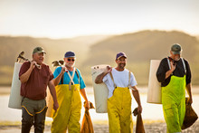 Group Of Fisherman On The Beach With Bags Of Shellfish.