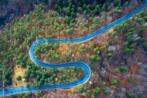 Garden Poster Air photo The aerial view of winding road from high mountain pass with trees in Transylvania, Romania, Curved road view by drone in the autumn-winter time