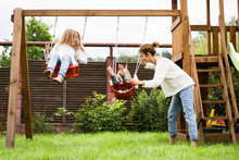Children On The Swing. Girls Sisters Swinging On A Swing In The Yard. Summer Fun.