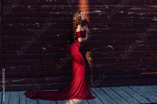 Photo Beautiful young woman in a long red evening gown with a train and black hat stan