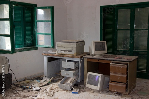 Grunge old abandoned office with drawers desks monitors and computers Wallpaper Mural