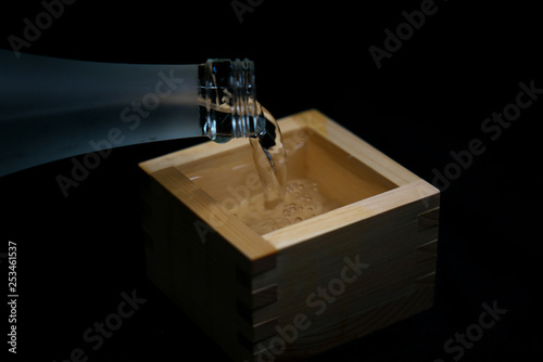 Tokyo,Japan-March 7, 2019: Pouring sake into a wooden container for drinking or Wallpaper Mural