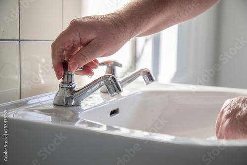 Poster Individuel Mann nutzt Waschbecken mit Leitungswasser zum Händewaschen