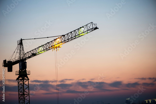 high-rise building crane on the background of the evening sky, building Fototapeta