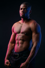 Muscular Man African Bodybuilder. Man Posing On A Black Background, Shows His Health And Perfect Shape.