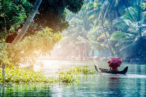 A man with an umbrella in a traditional boat sails through the backwaters of Alleppey in Kerala, South India Wallpaper Mural