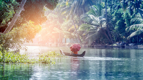 A man with an umbrella in a traditional boat sails through the backwaters of Alleppey in Kerala, South India. ALAPPUZHA KERALA
