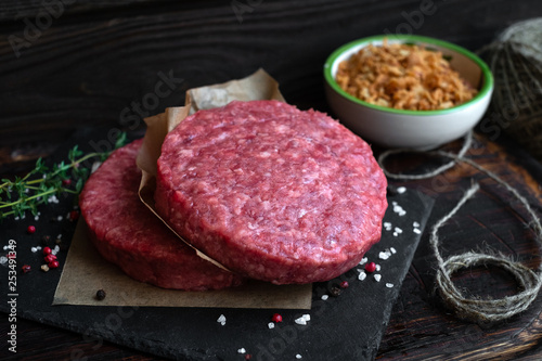 Fototapeta Raw Ground beef Burger cutlets with seasoning and fried onions on dark wooden board obraz