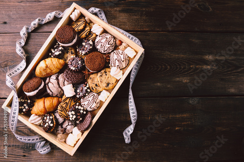 healthy lifestyle decision, motivation, diet restrict, carbs reduce, sugar, sweets. chocolate cookie background and measure tape with copy space. fitness, nutritionist, dietitian blog design concept