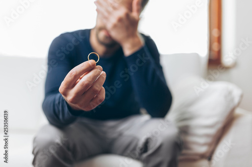Heartbroken man holding a wedding ring Wallpaper Mural