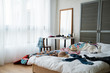 Large suitcases and bag packing for summer journey in room on wooden floor. messy bedroom in cozy apartment with fashion colorful cloth on white bed in morning. cosmetics on dress table by mirror.