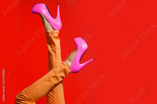 Female legs wearing summer high heels over red background