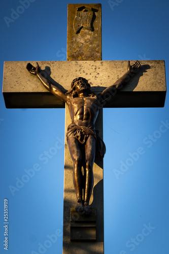 Fotografie, Obraz  Beautiful stone cross crucifix with Jesus Christ bronze sculpture hit by sunset light on a blue sky