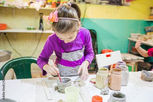 Keuken foto achterwand Koken Little Girl At Pottery Workshop Painting Clay Vase