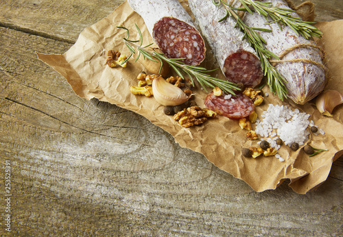 Photo sur Toile Amsterdam Italian salami wih sea salt, rosemary, garlic and nuts on paper. Rustic style. Close up.