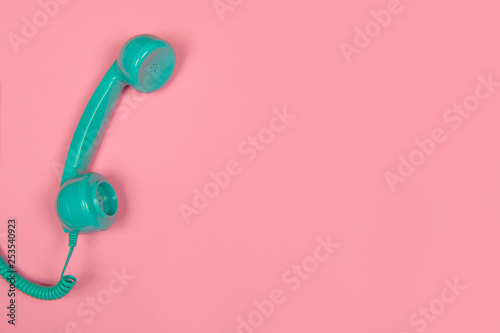 Blue retro telephone on a pink background with copy space - 253540923