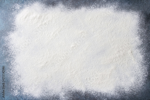 Photo Stands Bread Sifted wheat flour over dark blue texture surface. Food background.