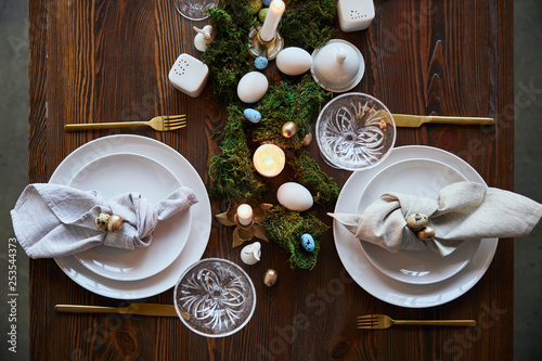 Foto op Plexiglas Europa top view of quail eggs on napkin and plates near green moss, candles and crystal glasses on wooden table
