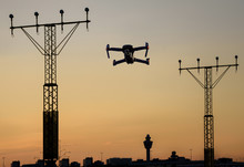 Unmanned Drone Flying Near Runway At Airport In Between Approaching Runway Lighting At Sunset