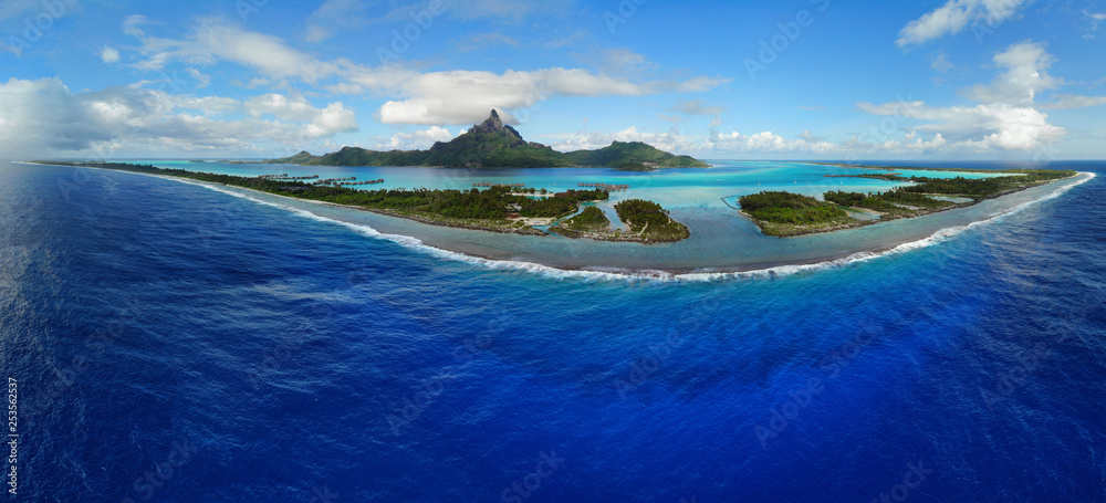 Fototapeta Aerial panoramic landscape view of the island of Bora Bora in French Polynesia with the Mont Otemanu mountain surrounded by a turquoise lagoon, motu atolls, reef barrier, and the South Pacific Ocean