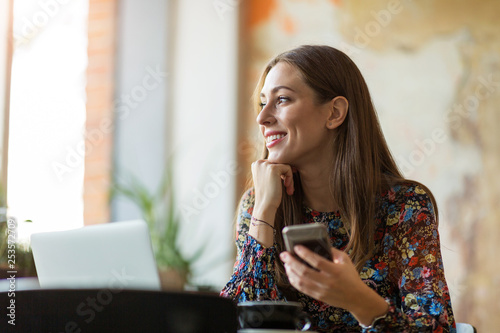 Obraz Young woman with laptop in cafe - fototapety do salonu