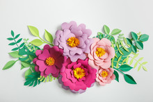 Top View Of Pink And Lilac Paper Flowers With Green Leaves On Grey Background
