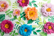 Top View Of Colorful Paper Flowers And Green Leaves On Grey Background
