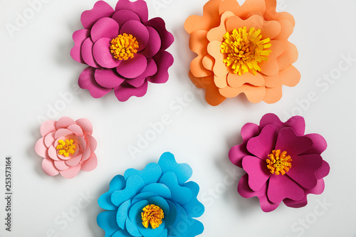 top view of multicolored paper flowers on grey background