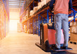man worker with electric forklift working in warehouse.