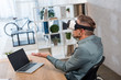businessman wearing virtual reality headset while sitting near laptop with blank screen
