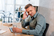 handsome man holding glass of water while having headache in office