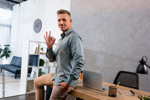 Valokuvatapetti happy businessman showing ok sign while sitting with hand in pocket in office