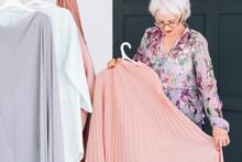 Wealthy Senior Lifestyle. Fashion Clothes Shopping. Confident Elderly Lady Trying On Elegant Garment.